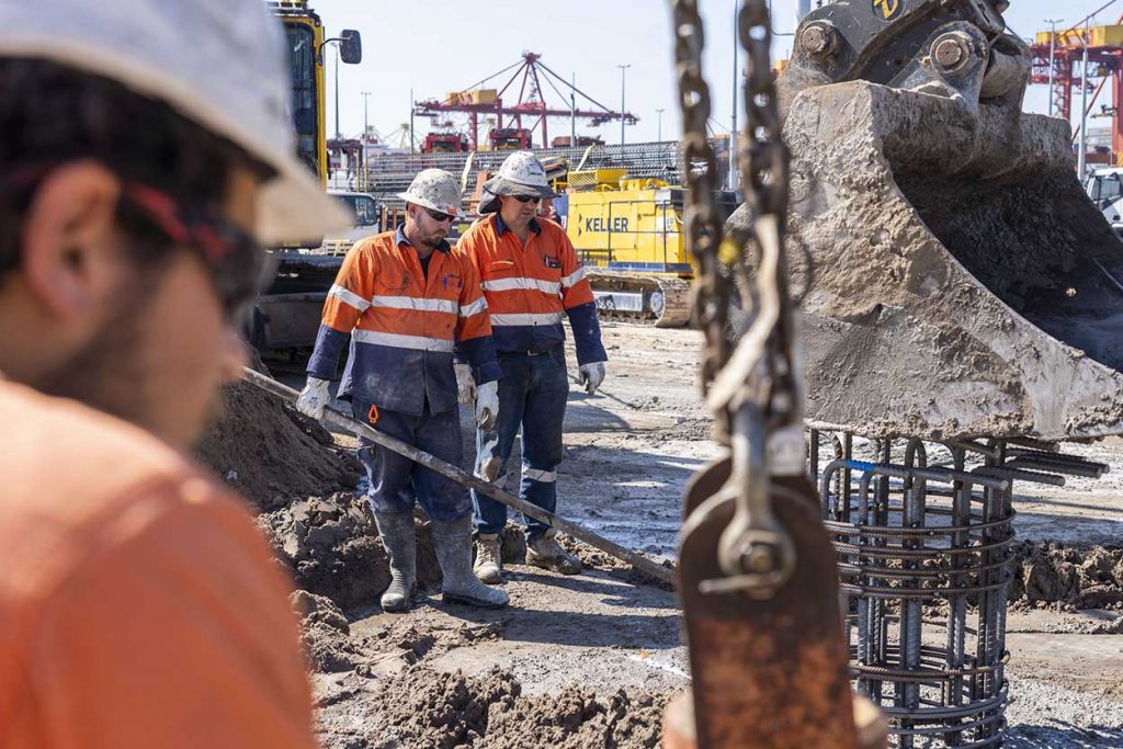 Workers guiding a steel cage into a piling hole for ground footings