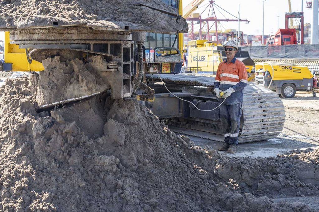 A smiling working watching at the piling hole is being dug